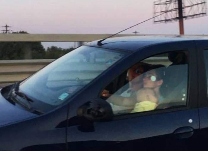 FOTO / O femeie a fost surprinsă în timp ce conducea cu bebeluşul în braţe. Gestul poate fi mortal! Fotografiile au ajuns virale