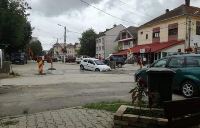 FOTO / O femeie din Caransebeș s-a trezit cu mașina înfiptă în asfalt, la propriu. Imaginile sunt virale