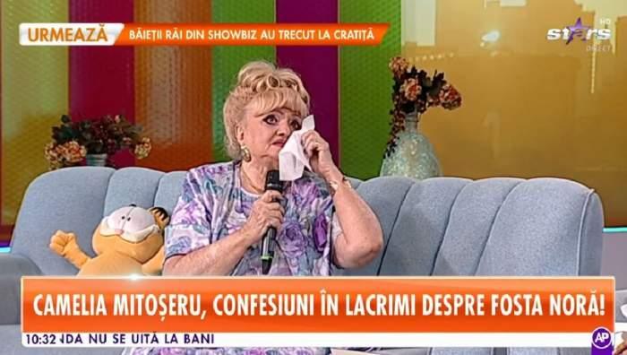 Camila Mitoșeru își șterge lacrimile cu un șervețel. Vedeta stă pe canapea.