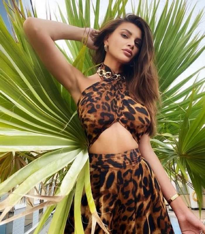 Ramona Gabor poarta o rochie decupata cu imprimeu de leopard, tine mana in par