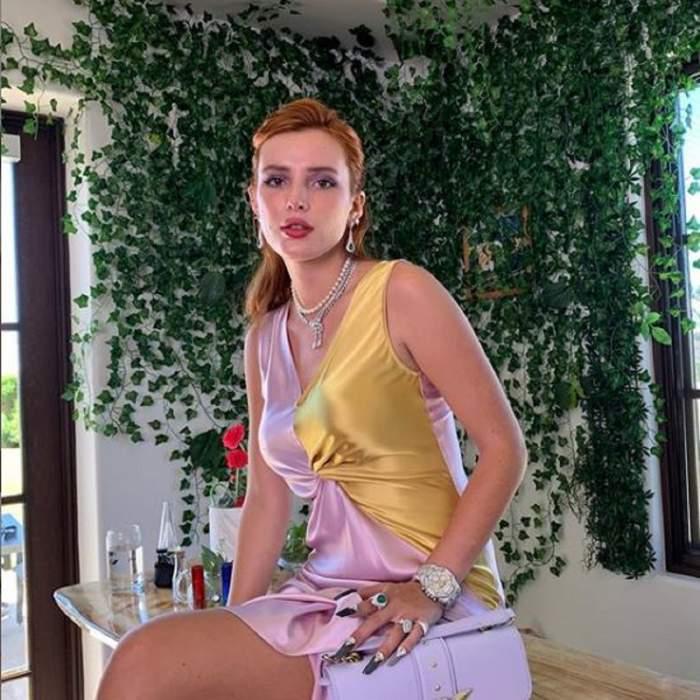 Bella Thorne poarta o rochie aurie cu violet, are parul prins si sta pe o masa