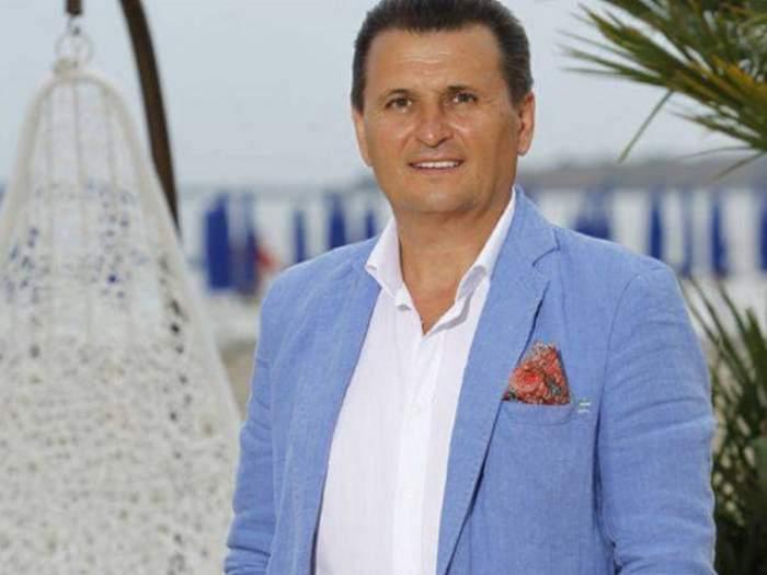Nea Marin poarta un sacou albastru si camsa alba, este pe plaja