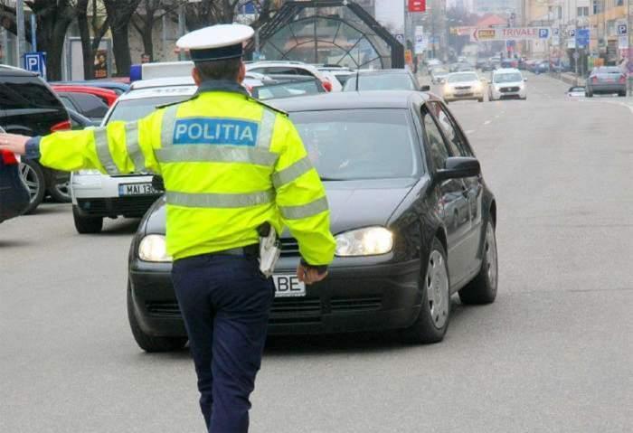 Un polițist îi face semn unui șofer.