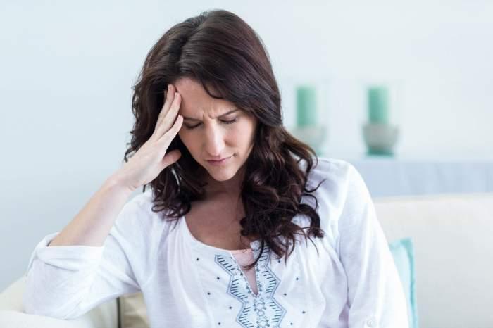 Femeie brunetă în bluză albă cu dureri de cap