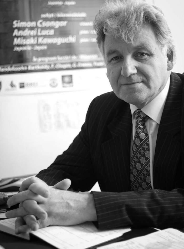 Vasile Cazan sta la birou si poarta costum