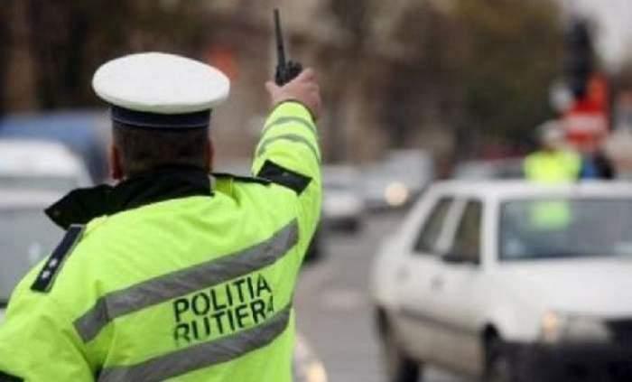 Un polițist de frontieră îi face semn unui șofer. Acesta este așezat cu spatele.