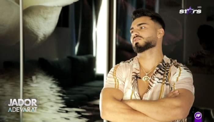 Jador poartă o cămașă de vară, albă. Artistul își ține brațele încrucișate.