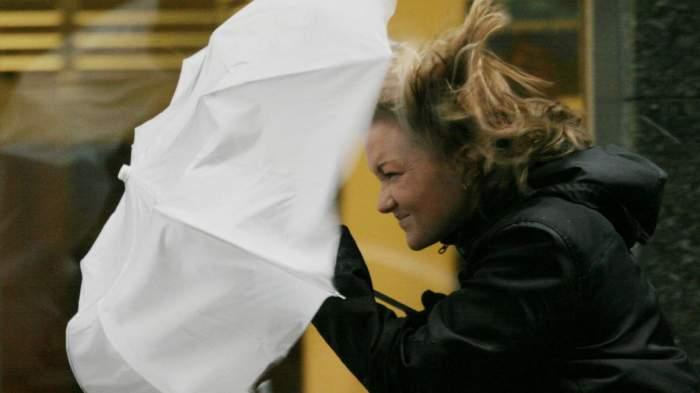 Femeie cu umbrelă se luptă cu vântul puternic