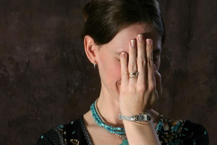 Femeie rușinată cu mâna la față