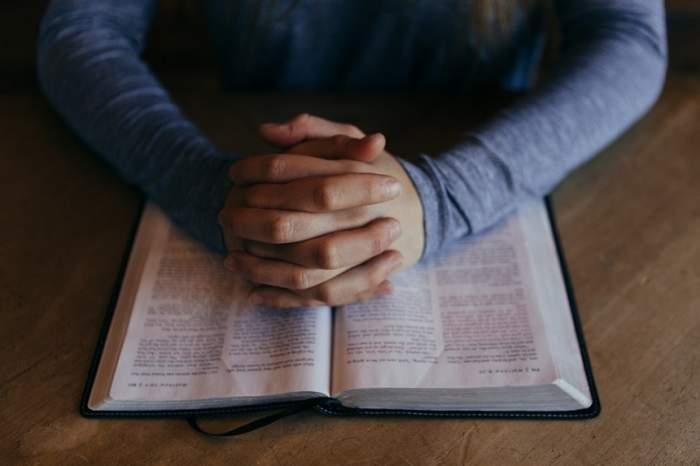 Fotografie cu o persoană care citește rugăciuni dintr-o carte