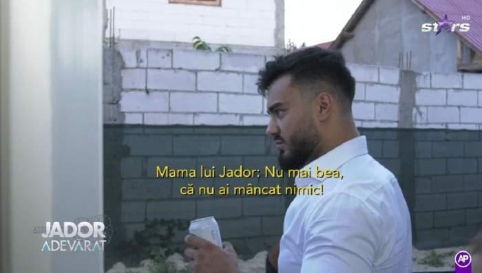 Jador poartă un tricou alb. Artistul se uită nedumerit la mama lui.