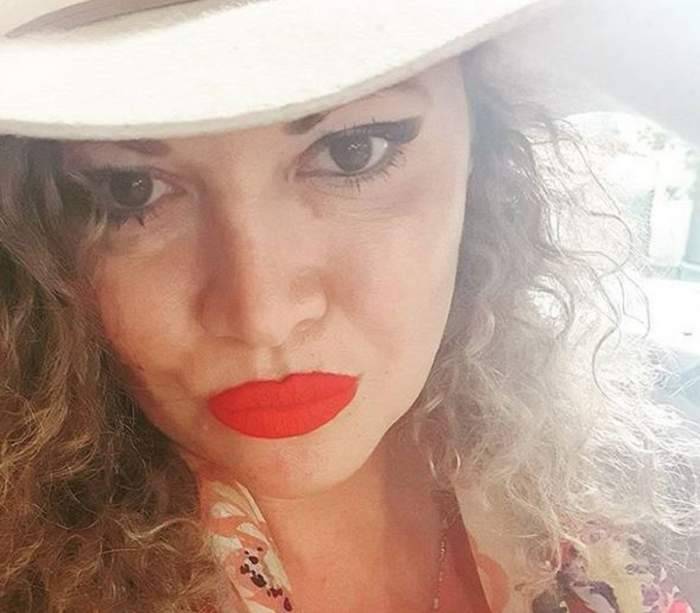 Oana lis poartă o pălărie crem. Vedeta este dată cu ruj roșu pe buze.