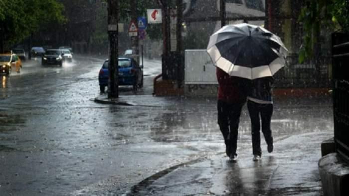 Fotografie pe timp de ploaie cu două persoane sub o umbrelă