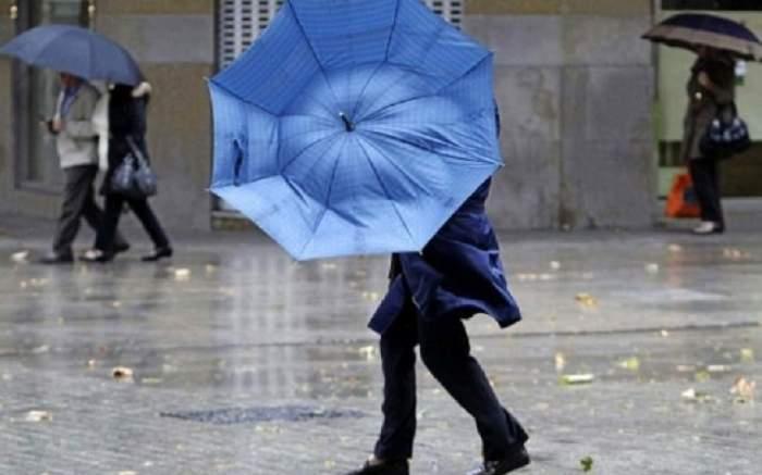 Femeie cu umbrela zburată de vânt