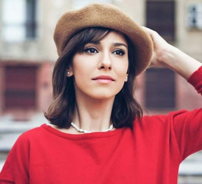 Fotografie cu Dana Rogoz purtând o ținută roșie și o pălărie crem