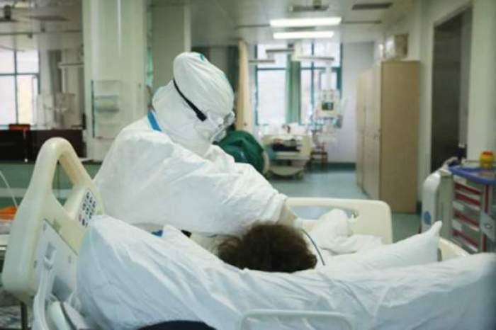 Medic care îngrijește un pacient, aflat pe patul de spital