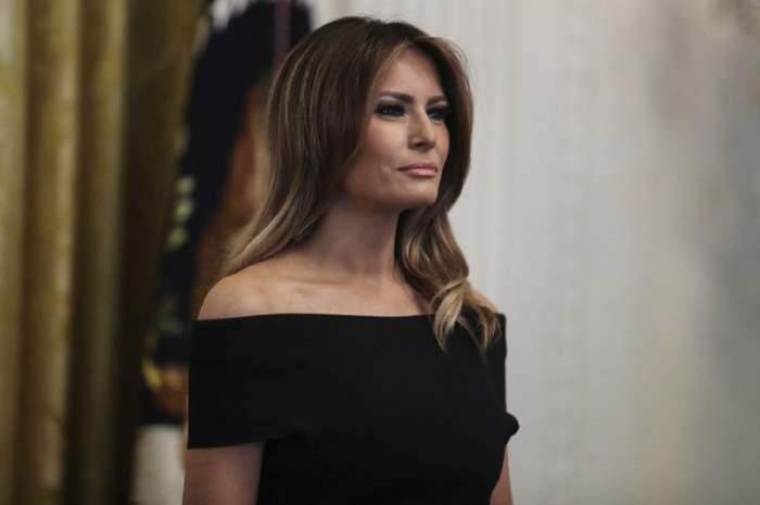 Melania Trump poarta o rochie neagra, fara umeri si parul desprins pe spate