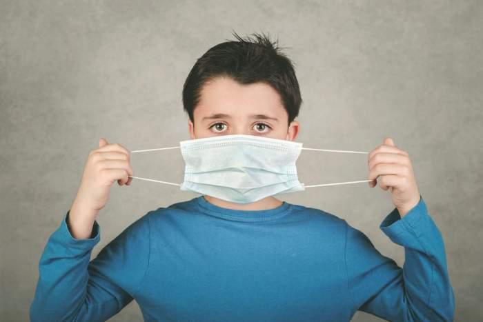 Copil cu bluză albastră și mască chirurgicală