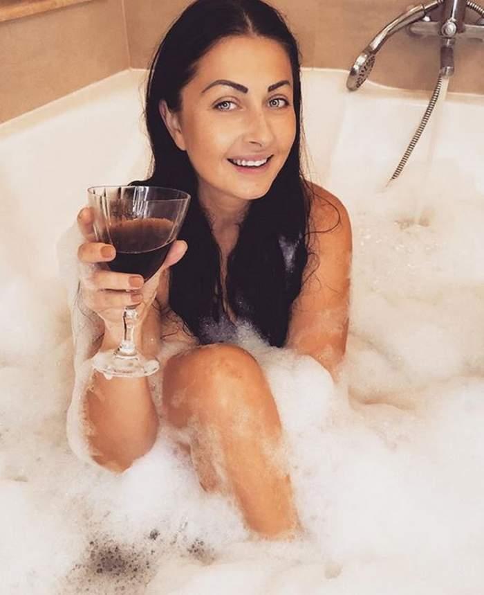 Gabriela Cristea este goală, în cadă. Vedeta este acoperită de spumă și ține în mână un pahar de vin.