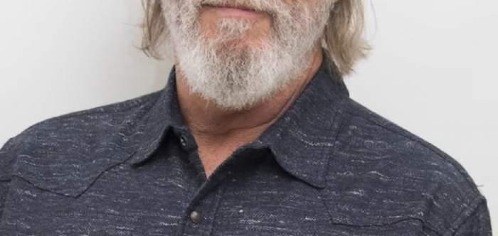 Jeff Bridges poartă un tricou gri. Actorul zâmbește.
