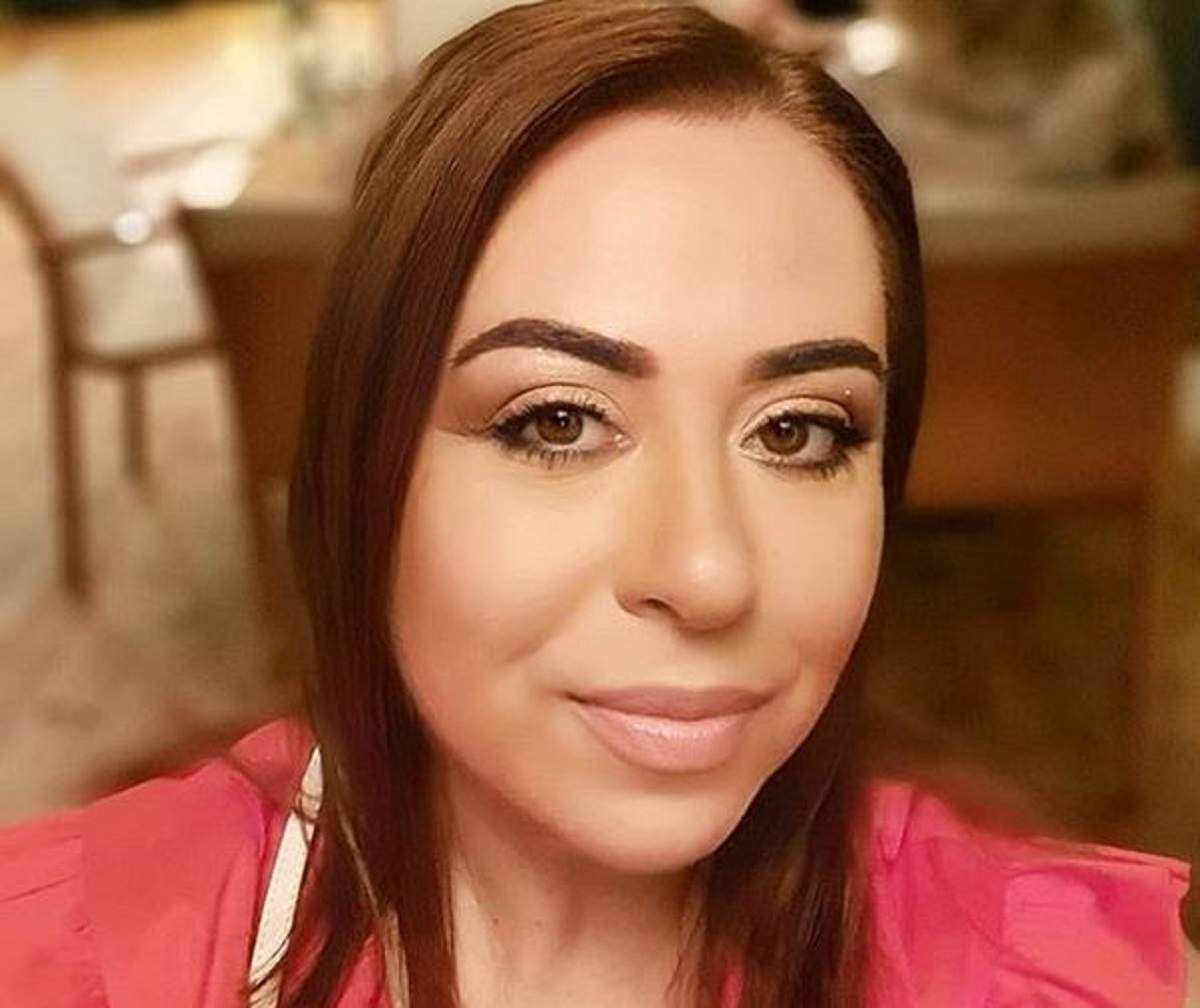 Oana Roman e îmbrăcată cu o bluză roz. Vedeta zâmbește slab.