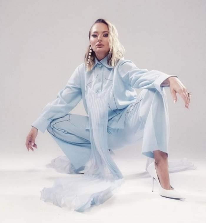 Delia poarta un costum bleu si sta ghemuita