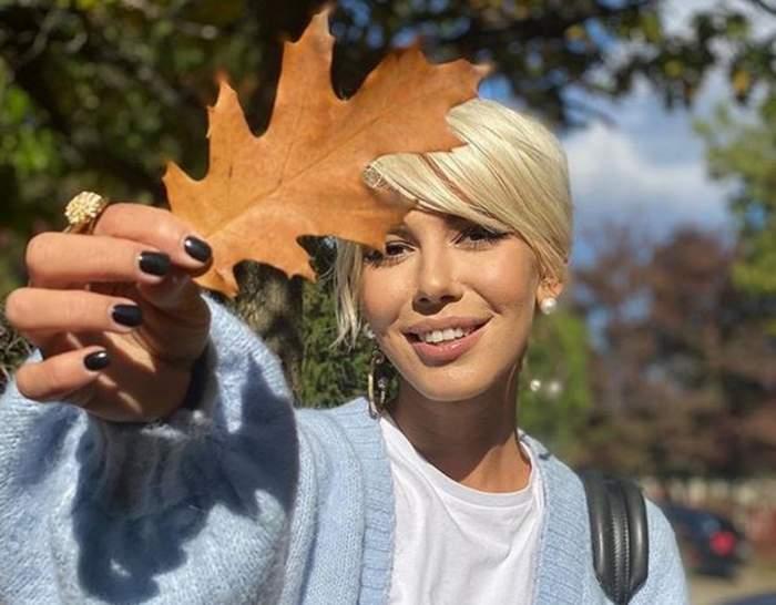 Sore ține o frunză în mână. Artista poartă un pulover bleu.