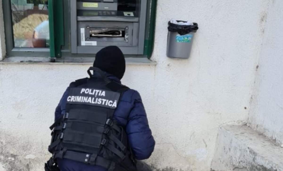Imagine cu un politist in fata unui atm distrus