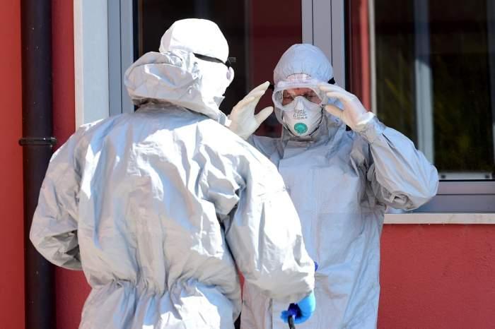 Doi medici, îmbrăcați corespunzător pandemiei, stau de vorbă