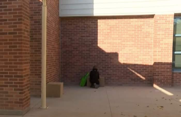 Un băiețel de 9 ani stă pe jos și își face temele pe trotuarul de lângă școală. Laptopul lui este așezat pe o cutie de carton.