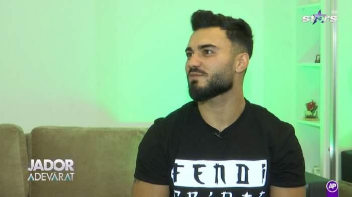 Jador poartă un tricou negru. În spatele lui este o canapea.