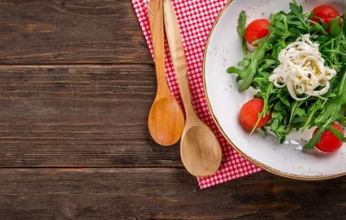 Un platou cu mâncare. Lângă farfurie sunt două linguri de lemn, pe masă.