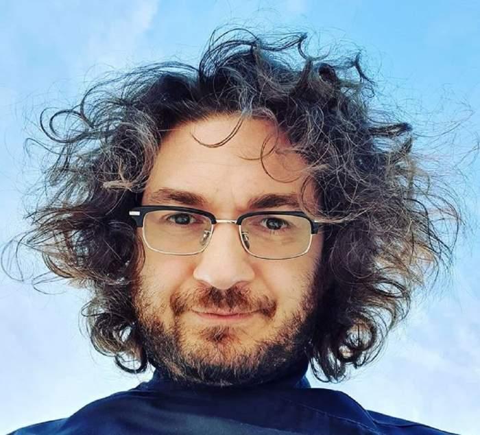 Florin Dumitrescu poartă ochelari de vedere. În spatele lui se vede cerul.