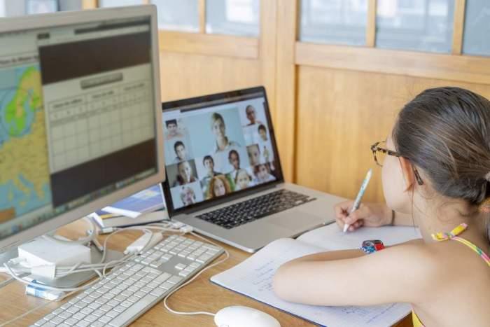 O fetiță care asistă la cursurile online