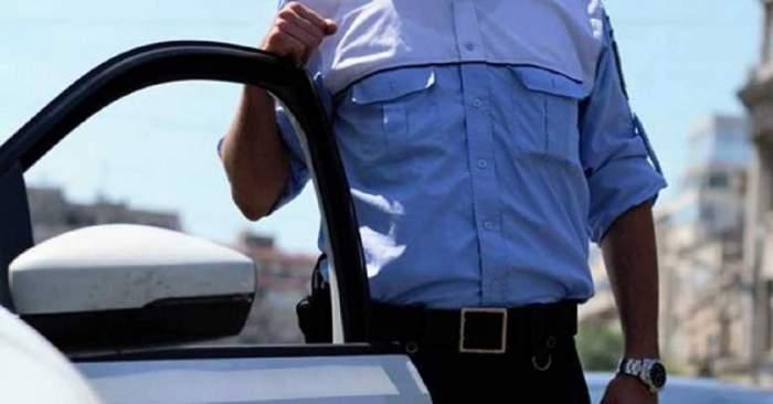 Bust polițist în cămașă lângă o portieră deschisă