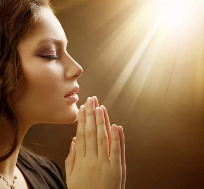 O femeie care se roagă. Aceasta ține palmele lipite.