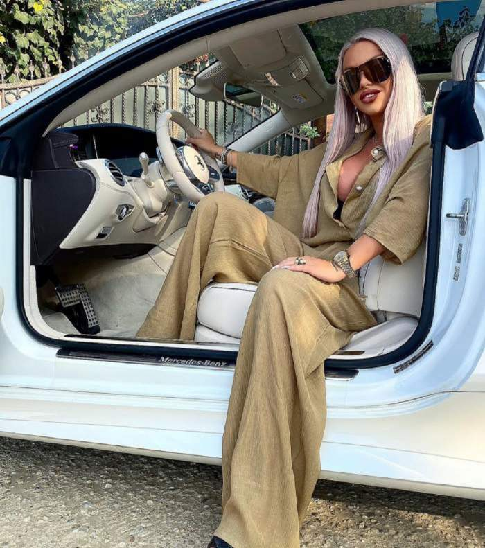 Loredana Chivu poarta o salopeta kaki si sta in masina cu mana pe volan