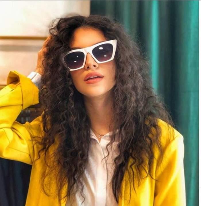 Cleopatra Stratan poarta ochelari se soare albi, un blazer galben si are parul cret