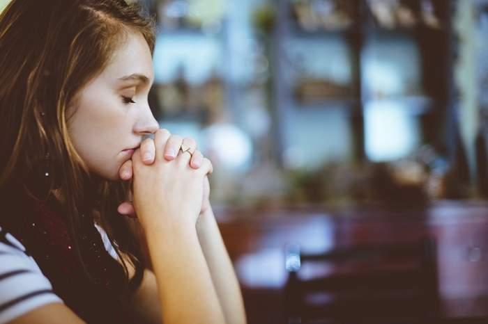 Fotografie cu o fată care se roagă
