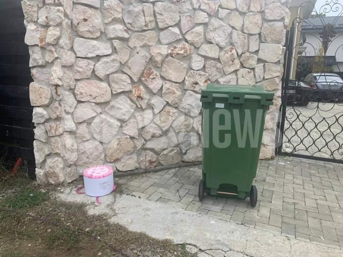Poarta lui Alex Bodi. Lângă gunoi este un buchet de flori roz.