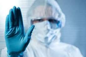 Medic îmbrăcat în combinezon spune stop COVID-19