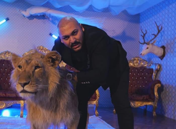 Dani Mocanu, în sacou negru alături de un leu.