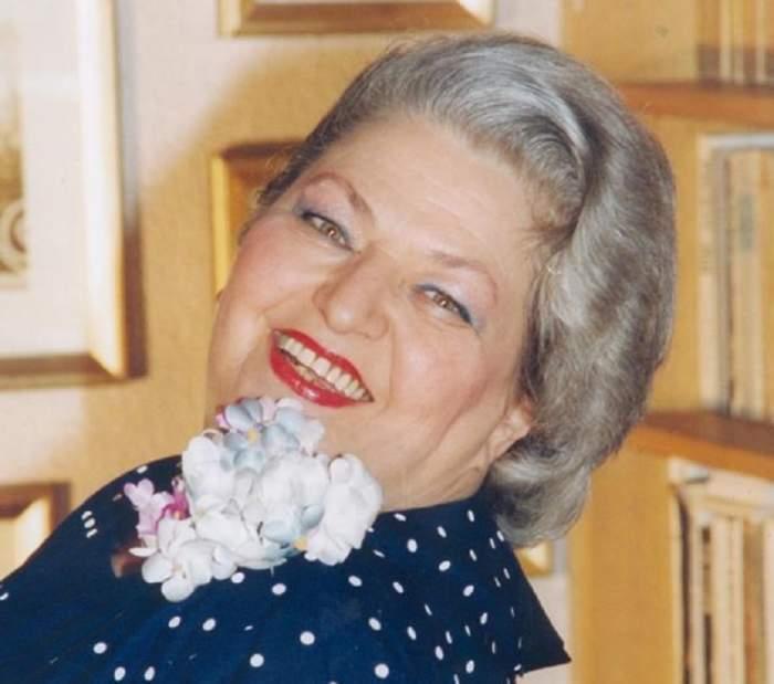 Draga Olteanu Matei a fost fotografiată zâmbind, într-o bluză cu o floare mare pe umăr