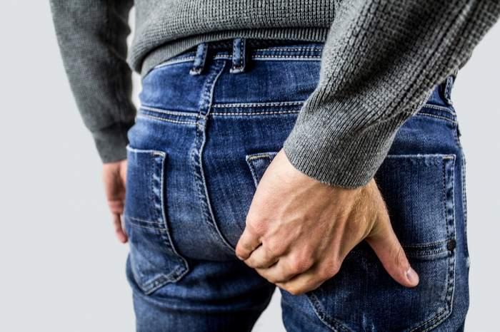 Fotografie cu un bărbat ce-și ține mâna pe posterior