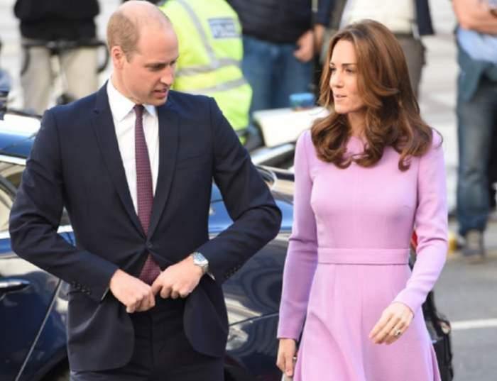 Prinţul William şi Kate Middleton merg pe stradă. El poartă in costum negru, iar ea o rochie roz.