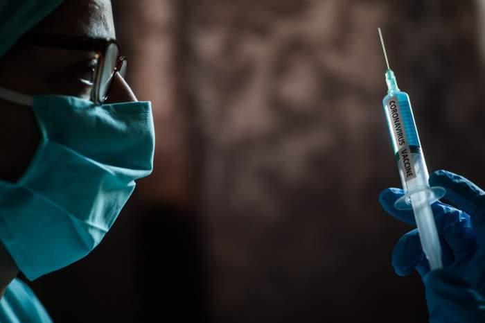 Un medic poarta masca si tine vaccinul in mana