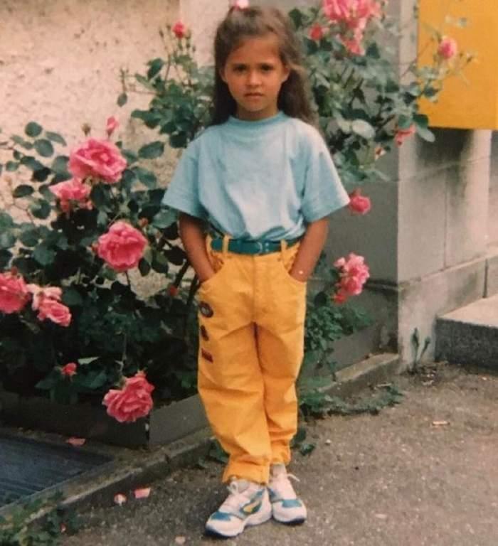 Antonia într-o poză realizată în copilărie. Artista purta un tricou bleu și pantaloni oranj. În spatele ei este o tufă de trandafiri roz.