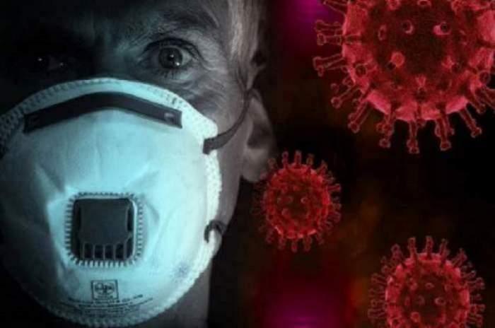 Un bărbat care poartă mască de protecție. În spate este o ilustrație cu viruși.