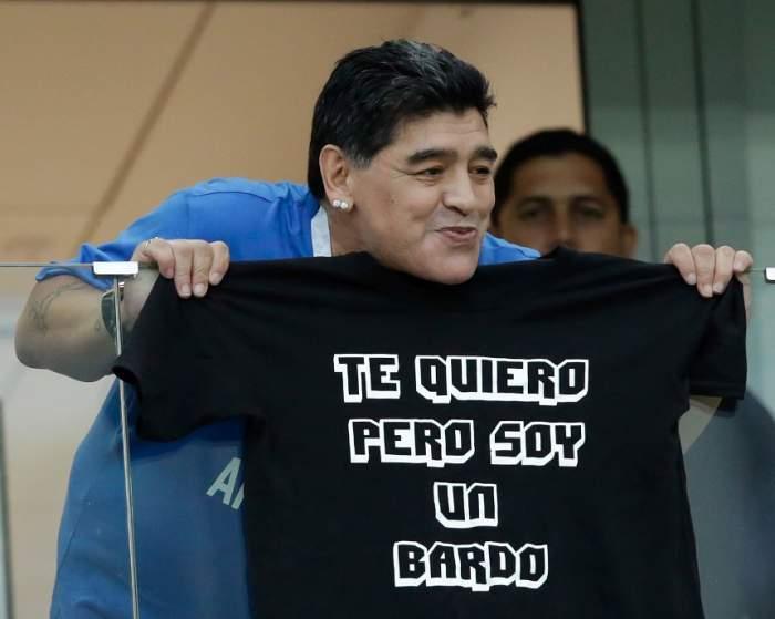 Diego Maradona, aflat la tribună, ține în mâini un tricou cu o inscripție