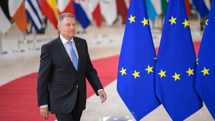 Klaus Iohannis, fotografiat zâmbitor lângă steagurile UE